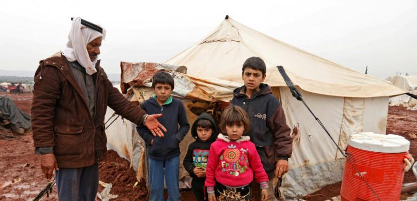 Abou Khaled pose avec ses enfants dans un camp de fortune de déplacés à Batabou, à la frontière entre les provinces syriennes d'Idleb et d'Alep, le 24 janvier 2018