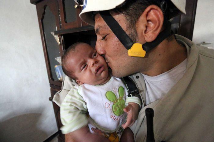 Un casque blanc syrien, embrasse un bébé après l'avoir sauvé.